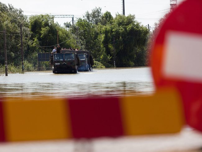 Army trucks are crossing a flooded closed road în Șendreni, Romania on July 3rd, 2010.