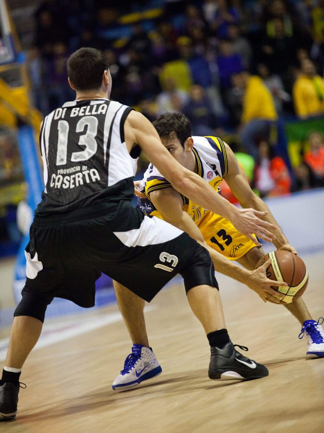 Two basketball players are fighting for the ball in a match between Pepsi Caserta (IT) and Sutor Montegranaro (IT) in Porto San Giorgio, Italy on December 18th, 2010.