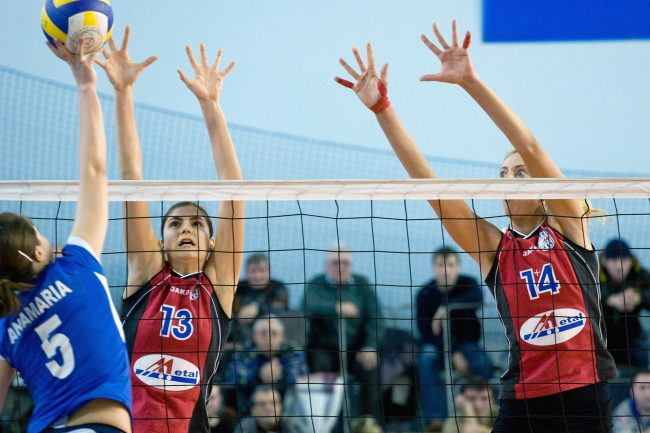 Voleyball players are fighting over the ball in a game played in Galați, Romania on February 18th, 2010.