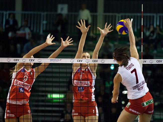 Volley players are playing in a CEV Cup match between Scavolini Pesaro (IT) and Dinamo București (RO) in Pesaro, Italy on December 8th, 2010.